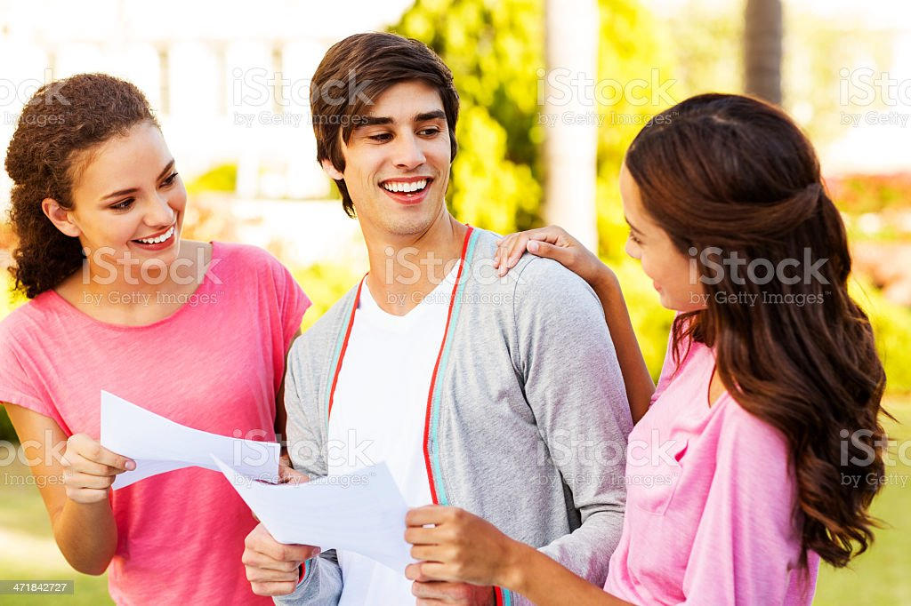 Students With Test Results Looking At Friend On Campus royalty-free stock photo