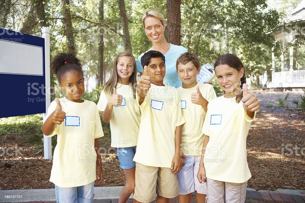 Students with their teacher giving a thumbs up sign royalty-free stock photo