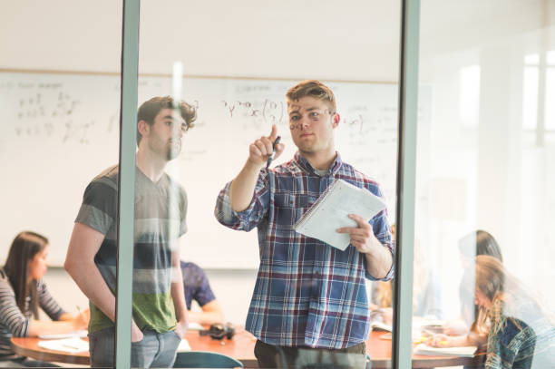 students work on math problem together in conference room. they are writing the equation on the whiteboard - day in the life series stock pictures, royalty-free photos & images