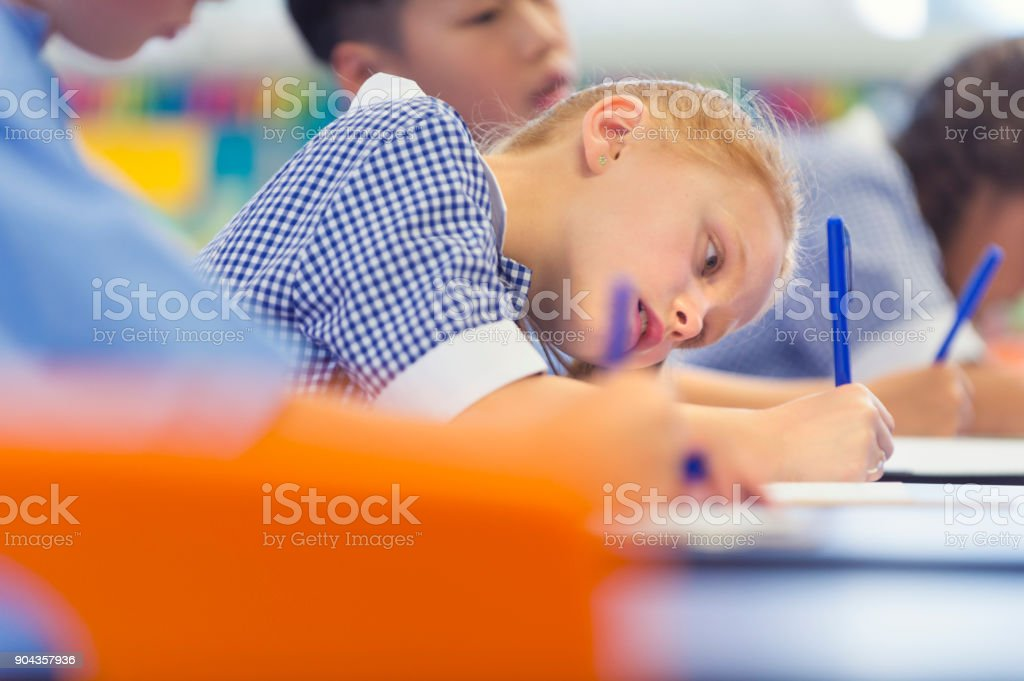 Students working at their desk. In focus is a Caucasian student very...