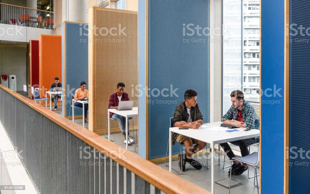 Students working in modern study cubicles at FE college стоковое фото