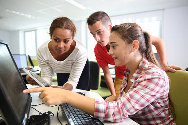 Students working together in computing class stock photo