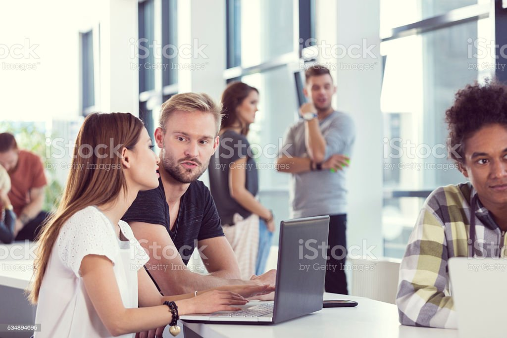 Students working together on laptop at the university Multi ethnic group of students working in groups at the university. Focus on couple using laptop. 2015 Stock Photo