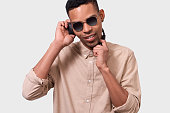 istock Studio close up portrait of African American young man with headphones listen the music. Happy handsome smiling Afro male DJ wearing mirror sunglasses and casual outfit, posing over white studio wall. 1139078975
