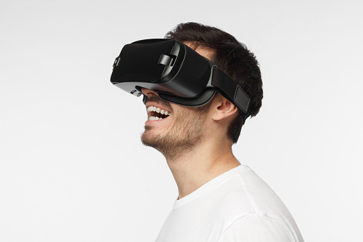 Studio closeup of young happy Caucasian man with face hair isolated on grey background smiling positively while experiencing virtual reality with help of special headset, enjoying his free time