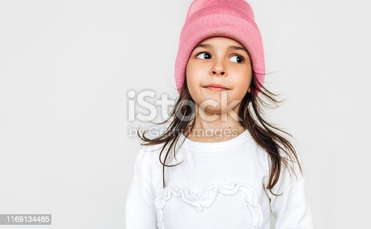 istock Studio closeup portrait of pleased little girl smiling and looking to one side, wearing white sweater and knitted pink hat, posing over light gray wall. Beautiful child waiting for a Christmas time. 1169134485