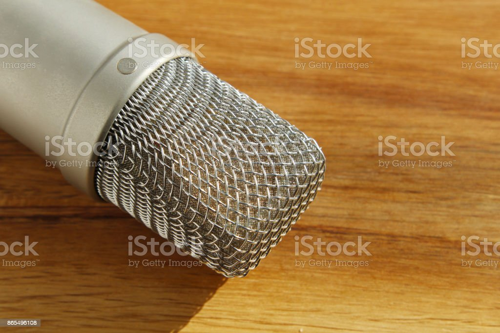A studio condenser microphone on a wooden board. This image can be used to represent music recording or pod casting. stock photo
