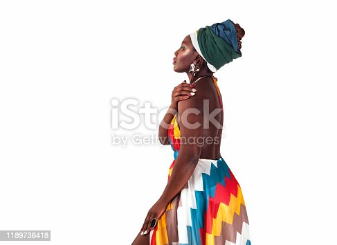 Studio fashion portrait of young African ethnicity woman in summer colorful dress and ethnic head wrap. Isolated white background.