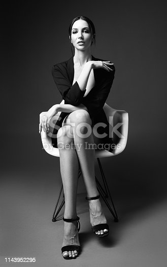 Studio fashion shot of the gorgeous young woman sitting on chair. Portrait of beautiful girl dressed in black jacket and sandals. Seductive lady (black and white)