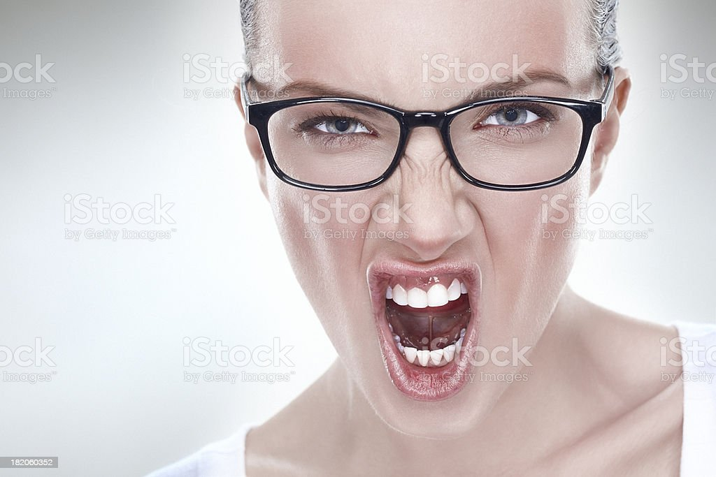 Studio headshot of a young angry flushed woman screaming stock photo