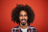 Studio headshot of young trendy spanish man. Plain background. Mixed reace model with curly hair.