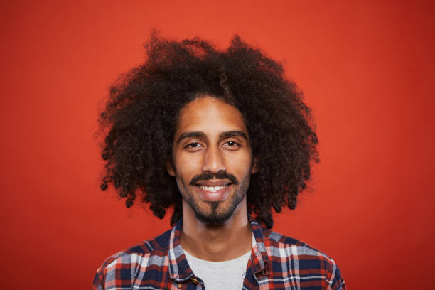 Studio headshot of young trendy spanish man. Studio headshot of young trendy spanish man. Plain background. Mixed reace model with curly hair. rastafarian stock pictures, royalty-free photos & images