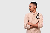 istock Studio horizontal portrait of African American young man with headphones on shoulders, looking at the blank copy space. Afro male wearing mirror sunglasses, casual shirt, posing on white studio wall 1153638234