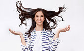 istock Studio image of beautiful young woman with flying hair smiling broadly and looking at he camera with raised hands, posing over white background. Charming brunette female with beautiful long hair 1153670779