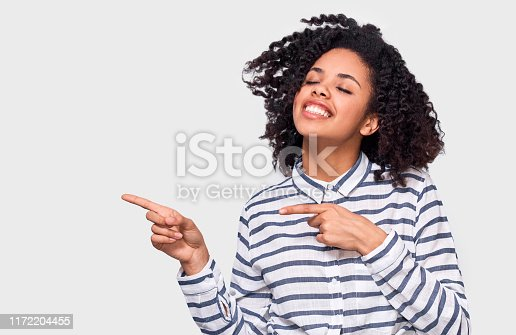 Studio image of happy African American young woman dressed in striped shirt, indicates aside with forefinger to blank copy space, isolated over white wall.