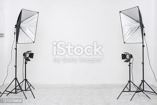 Empty studio with lights on white wall. Copy​ space​ for​ text or​ mock-up
