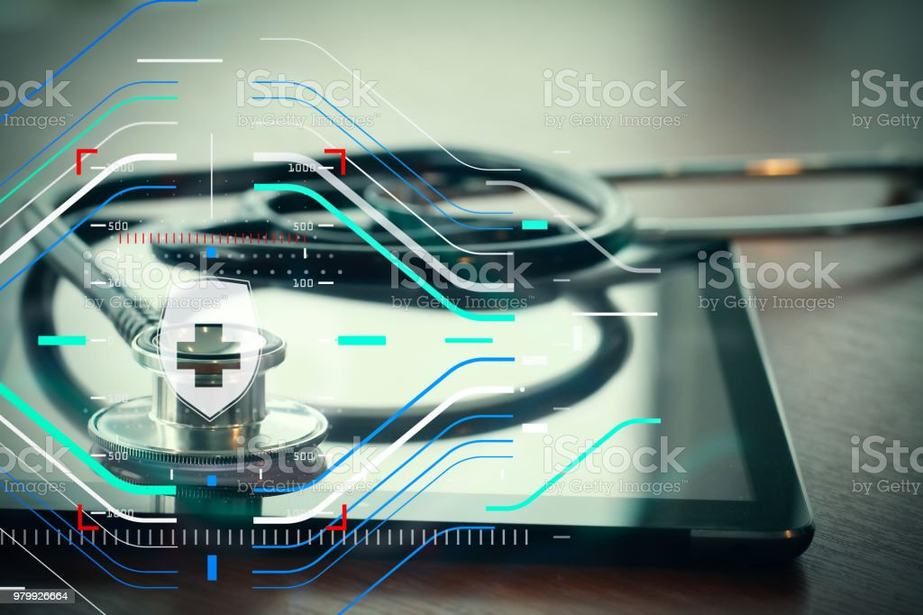 Studio macro of a stethoscope and digital tablet with shallow DOF evenly matched abstract on wood table background copy space stock photo