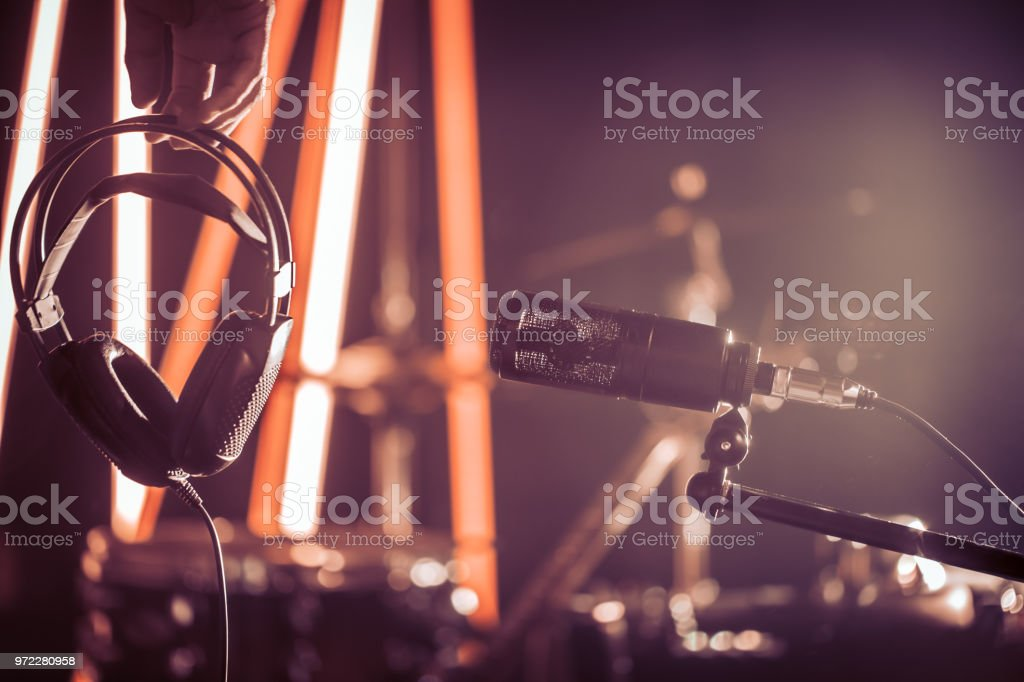 Studio microphone and headphones in the hand of a person close up, in a recording Studio or concert hall. stock photo