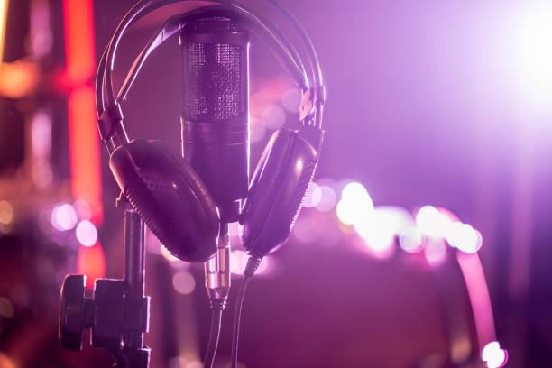studio-mikrofon und kopfhörer mit einer großaufnahme stehen in einer aufnahme studio oder konzertsaal. - medium strähnchen stock-fotos und bilder