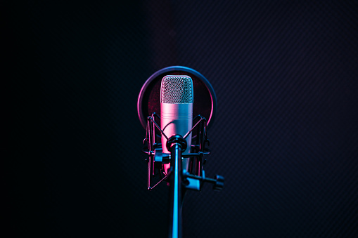Studio microphone and pop shield on mic in the empty recording studio with copy space. Performance and show in the music business equipment.