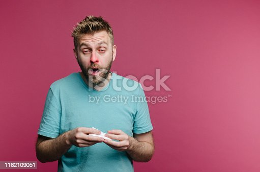 studio picture from a young man with handkerchief going to sneeze. Sick guy isolated has runny nose. man makes a cure for the common cold from the air conditioner
