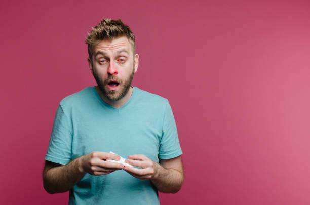 studiobild von einem jungen mann mit taschentuch gehen zu niesen. kranker kerl isoliert hat laufende nase. der mensch heilt die erkältung - erkältung und grippe stock-fotos und bilder