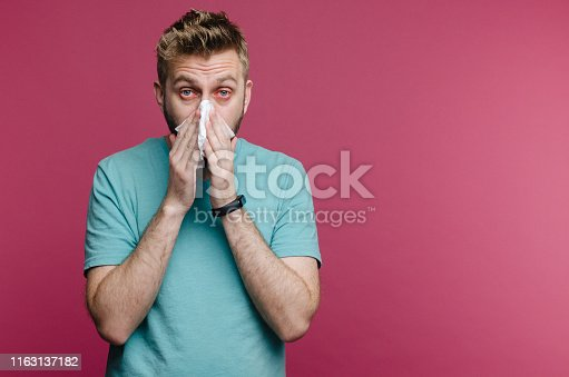 studio picture from a young man with handkerchief. Sick guy isolated has runny nose. man makes a cure for the common cold