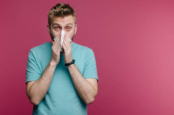 studio picture from a young man with handkerchief. Sick guy isolated has runny nose. man makes a cure for the common cold studio picture from a young man with handkerchief. Sick guy isolated has runny nose. man makes a cure for the common cold mucus stock pictures, royalty-free photos & images