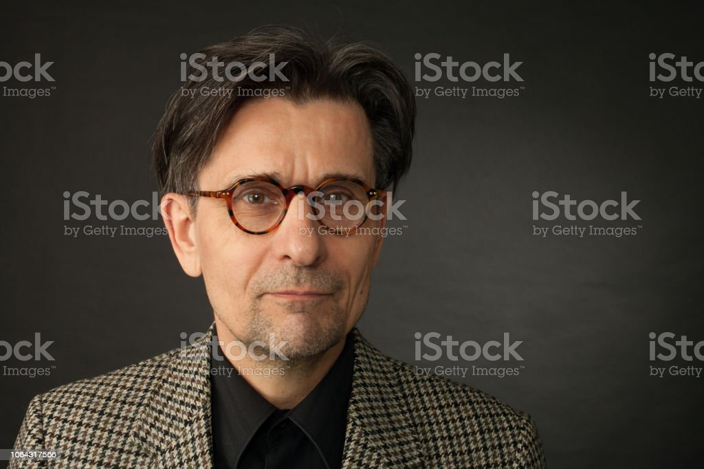 studio portrait of 60 year old man on black background studio portrait of 60 year old man in glasses on black background 55-59 Years Stock Photo