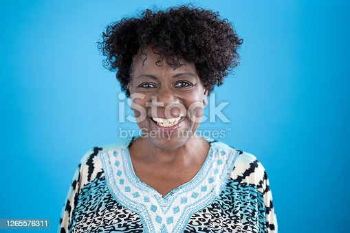Head and shoulders view of cheerful senior black woman with short curly hair wearing multi colored print top with border design against blue background.