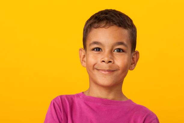 studio-porträt einer 10 jahre alten schüler auf gelbem hintergrund - schulkind nur jungen stock-fotos und bilder