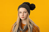 Studio portrait of a 12 year old blonde girl in a brown sweater and knitted hat on a yellow background