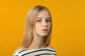 Studio portrait of a 12 year old blonde girl on a yellow background