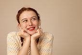 istock Studio portrait of a 20 year old attractive red-haired woman on a beige background 1163053119