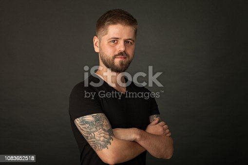 Studio portrait of an attractive 25 year old bearded tattooed man in a black t-shirt on a black background.