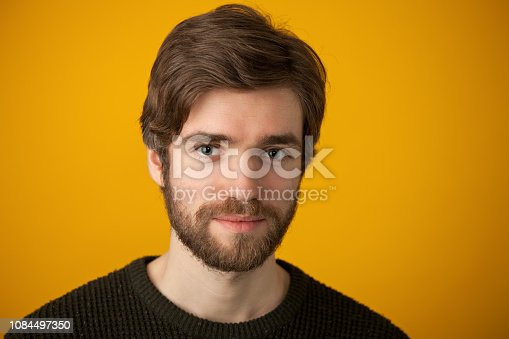 Studio portrait of a 25 year old bearded man in a sweater on a yellow background