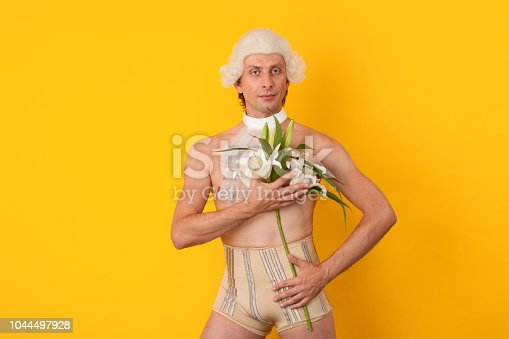 studio portrait of a 35 year old man in a white wig with a lily on a yellow background