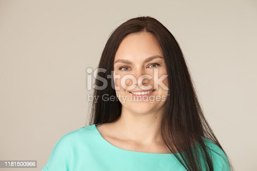Studio portrait of a 40 year old woman in a turquoise blouse on a beige background