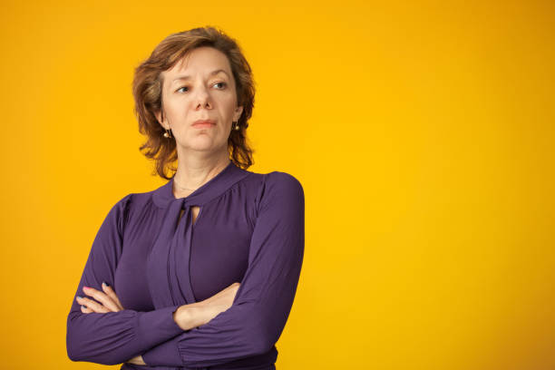 Studio portrait of a 40 year old woman in purple blouse on a yellow background Studio portrait of a 40 year old woman in purple blouse on a yellow background arrogant stock pictures, royalty-free photos & images