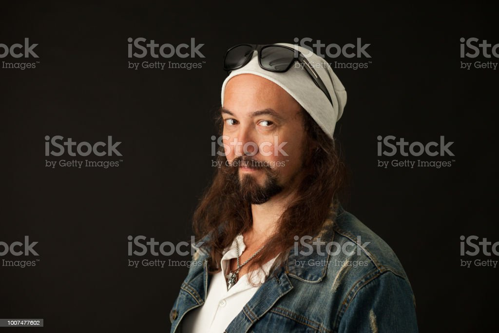 studio portrait of a 45 year old man with a beard on a black background stock photo