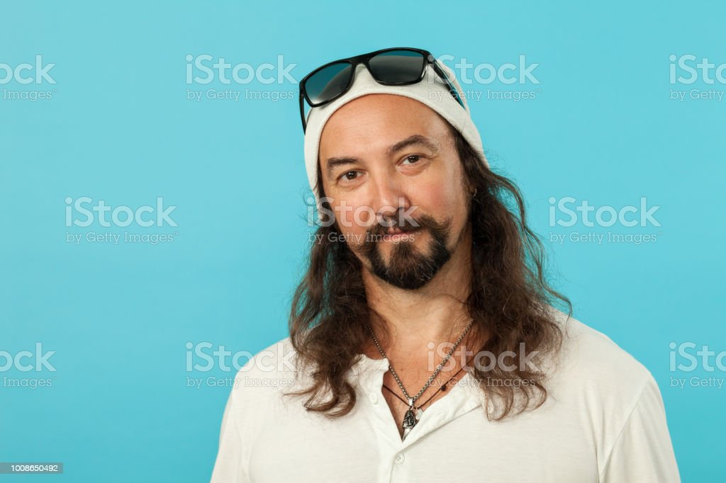 studio portrait of a 45 year old man with a beard on a blue background stock photo