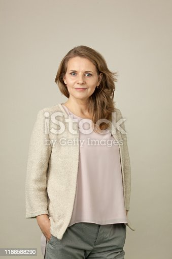 Close-up studio portrait of a 45 year old woman with long brown hair in a beige jacket on a beige background