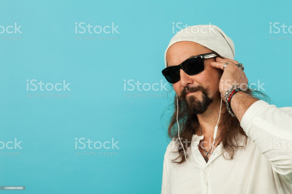 Studio portrait of a 45-year-old man with a beard in headphones on a blue background stock photo