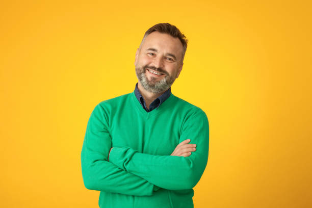 Studio portrait of a 50 year old bearded man in a green sweater on a yellow background Studio portrait of a 50 year old bearded man in a green sweater on a yellow background background color stock pictures, royalty-free photos & images