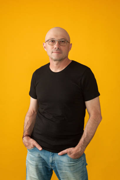 Studio portrait of a 50 year old man with a shaved head in a black T-shirt, jeans and glasses on a yellow background Studio portrait of a 50 year old man with a shaved head in a black T-shirt, jeans and glasses on a yellow background black shirt stock pictures, royalty-free photos & images