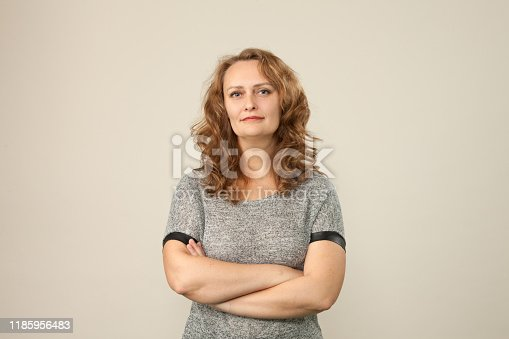 Close-up studio portrait of an attractive 50 year old woman with curly brown hair on a beige background