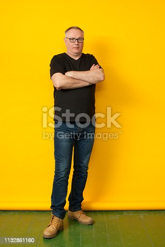Studio portrait of a 50 years old balding man in glasses and a black T-shirt on a black background