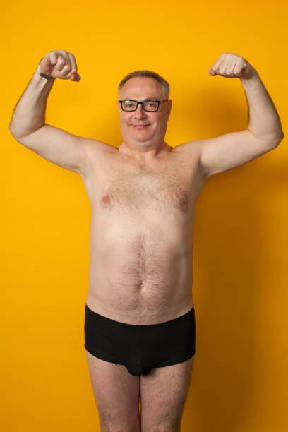 portrait de studio d'un homme bizarre de 50 ans dans un pantalon sur un fond jaune - homme slip photos et images de collection