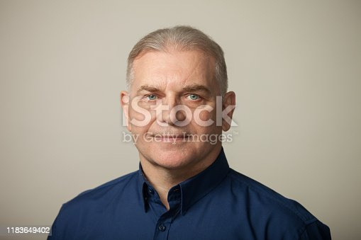 Studio portrait of a 60 year old businessman in a blue shirt on a beige background