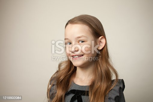 close-up studio portrait of a 9 year old girl with long brown hair in a gray dress on a beige background